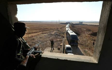 A member of Hayat Tahrir al-Sham group, led by Syria's former Al-Qaeda affiliate, watches as a convoy of buses gets ready to enter the towns of al-Foua and Kefraya to evacuate their residents on 18 July 2018. Picture: AFP.