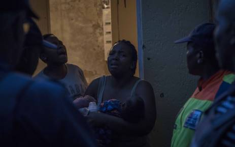 A woman and her family protest their arrest after returning to her room in a hijacked building where she was previously evicted. Picture: Thomas Holder/EWN