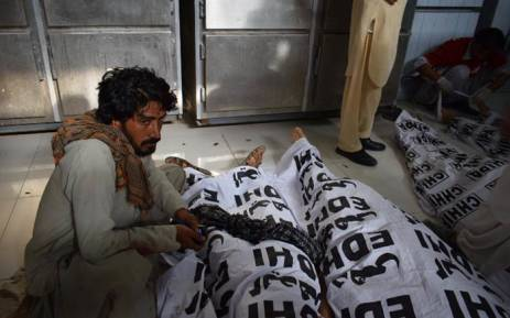 A Pakistani man sits next to a relative's dead body after a bomb blast at an election rally, at a hospital in Quetta on 13 July 2018. Picture: AFP.