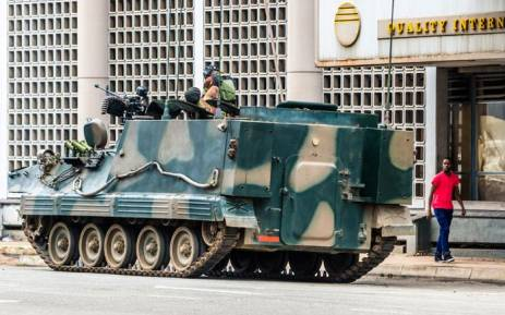 FILE: A man walks past a military tank parked on the side of a street in the Zimbabwean capital Harare on 16 November 2017. Picture: AFP.