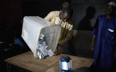 FILE: An election official overturns a box containing ballot papers during the vote counting at a polling station in Bamako on 12 August 2018, after the second round of Mali's presidential elections. Picture: AFP.