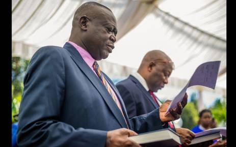 Former air force commander Perence Shiri (L), who was appointed Lands and Agriculture minister, takes his oath of office in a new cabinet which took oath of office at State House on December 4, 2017 in Harare. Picture: AFP.