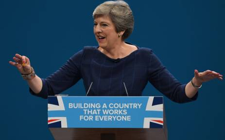 Britain's Prime Minister Theresa May holds up a throat sweet given to her as she delivers her speech on the final day of the Conservative Party annual conference at the Manchester Central Convention Centre on 4 October 2017. Picture: AFP.