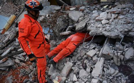 """Member of the """"Topos"""" (Moles) specialised rescue team search for survivors in Juchitan de Zaragoza, Mexico, on September 9, 2017 after a powerful earthquake struck Mexico's Pacific coast late on 7 September. Picture: AFP."""