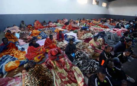 A picture taken on 11 December 2017 shows African migrants sitting in a shelter at the Tariq Al-Matar migrant detention centre on the outskirts of the Libyan capital Tripoli. Picture: AFP