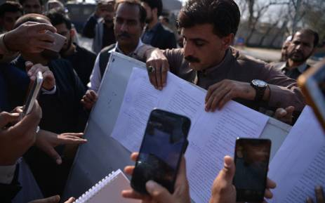 Pakistani local journalists take images of the court verdict against suspects accused in a blasphemy lynching case pasted on a notice board outside the central jail in Haripur district on 7 February 2018. Picture: AFP