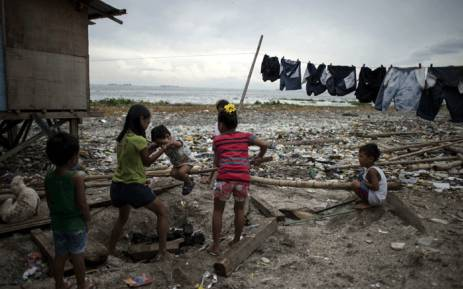 Children that live along the coast of Manila play together on 14 September, 2018 as preparations get underway for Super Typhoon Mangkhut to make landfall. Picture: AFP