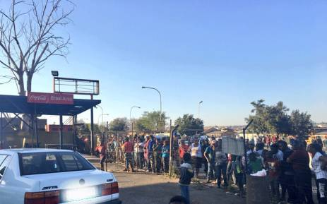 A large crowd of onlookers are gathered at a shopping complex in White City, Soweto, where some of the stores have been looted. Picture: Katleho Sekhotho/EWN
