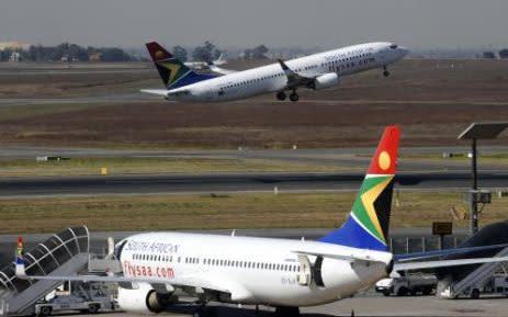 FILE: A South African Airways flight takes off as another one is parked in a bay on the tarmac at OR Tambo International airport in Johannesburg. Picture: AFP.