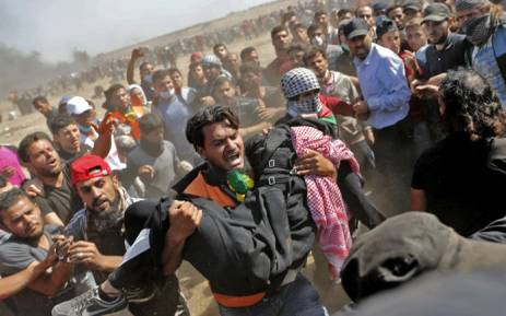 Palestinians carry a demonstrator injured during clashes with Israeli forces near the border between the Gaza strip and Israel east of Gaza City on 14 May 2018, during protests over the inauguration of the US embassy in Jerusalem. Picture: AFP