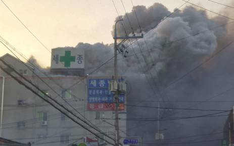Heavy grey smoke rises into the air from a fire at a hospital building in Miryang on 26 January 2018. Picture: AFP
