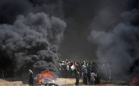 A Palestinian holds his national flag in the smoke billowing from burning tyres during clashes with Israeli forces near the border between the Gaza strip and Israel east of Gaza City on 14 May 2018. Picture: AFP