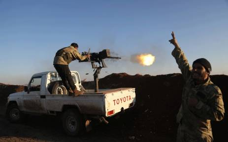 Turkish-backed fighters from the Free Syrian Army stand in the Tal Malid area, north of Aleppo, as they fire towards Kurdish People's Protection Units (YPG) positions in the village of Um al-Hosh, in the area of Afrin, on 20 January 2018. Picture: AFP.