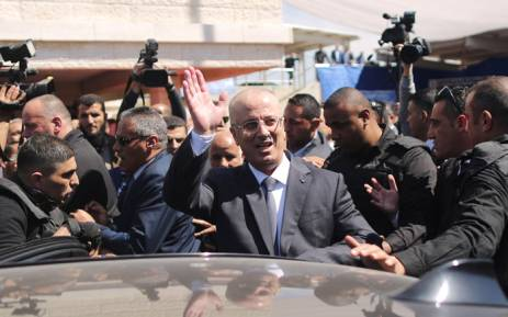 Palestinian Prime Minister Rami Hamdallah waves to the crowd upon his arrival in Gaza City on 13 March 2018. Hamdallah cut short a rare visit to Gaza on Tuesday after an explosion targeted his convoy, a source in the delegation said. Picture: AFP
