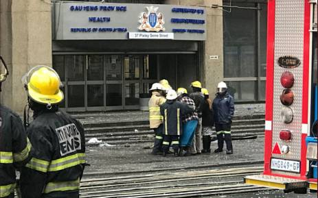Simphiwe Moropane's wife and his parents were taken to the site in front of the building where they stood briefly, crying and holding each other. Christa Eybers/EWN