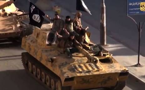 A screengrab taken from a video released on 1 July 2014, allegedly shows members of the IS (Islamic State) parading on top of a tank on a street in the northern rebel-held Syrian city of Raqqa. Picture: YouTube.