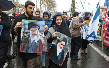 An Iranian man marches with a portrait of the country's Supreme Leader Ali Khamenei (L) alongside a woman holding up another of Islamic Revolution founder Ayatollah Ruhollah Khomeini (R) during a ceremony celebrating the 40th anniversary of Islamic Revolution in the capital Tehran on 11 February 2019. Picture: AFP