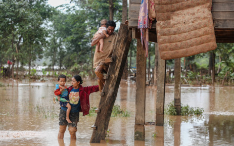 A couple carry their children from their home in the flooded area in Sanamxai, Attapeu province, of Laos on 26 July 2018. Picture: AFP.