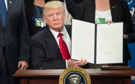 FILE: President Donald Trump signs an executive order to start the Mexico border wall project. Picture: AFP.