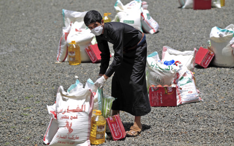 FILE: A Yemeni youth carries a portion of food aid, distributed by Yadon Tabney development foundation, in Yemen's capital Sanaa on 17 May 2020. Picture: AFP.