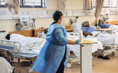 FILE: A hospital worker walks amongst patients in the COVID-19 ward at Khayelitsha Hospital, about 35km from the centre of Cape Town, on 29 December 2020. Picture: AFP.