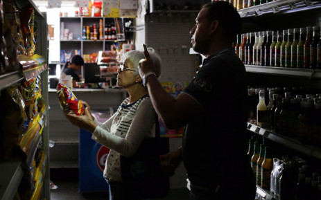 An employee uses his mobile phone torch to help a customer on 10 March 2019, during the third day of a massive power outage which has left Venezuelans without communications, electricity and water. Picture: AFP