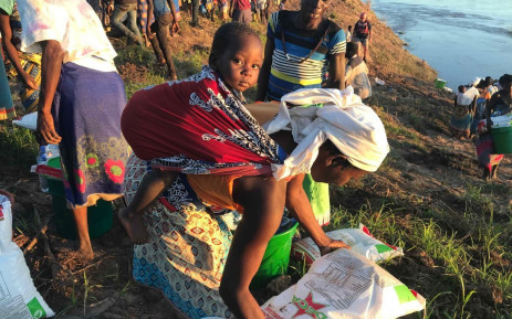 A mother gathers her food and water she received from the relief workers after Cyclone Idai hit Mozambique. Picture: Christa Eybers/EWN