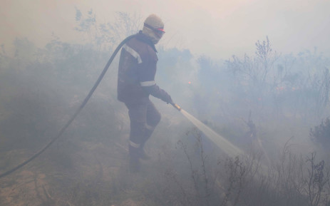 FILE: A firefighter walks through a thick cloud of smoke while putting out a fire. Picture: Bertram Malgas/EWN