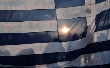 Protestors stand behind a huge Greek flag in front of the Greek parliament in central Athens, on 29 June 2015. Picture: AFP.