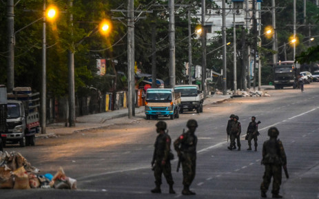 Soldiers keep watch as they block an empty street in Yangon on 10 March 2021, as security forces continue to crackdown on demonstrations by protesters against the military coup. Picture: AFP