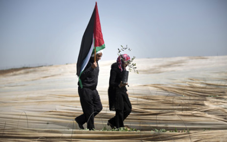 "A man holding a Palestinian flag and a woman carrying an olive tree, walk through rows of greenhouses on ""Land Day"" during which people notably plant olive trees on 29 March, 2014 near the Israeli border in Jabalia, in the northern Gaza Strip. Picture: AFP."