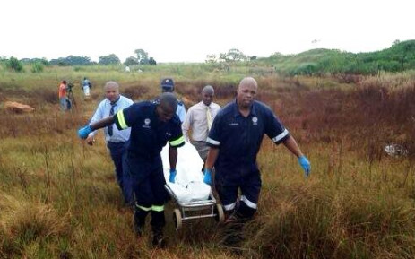 Forensic pathologists carry the body of one of the girls found dead in Dobsonville, Soweto, on 19 February 2014. Picture: Masego Rahlaga/EWN.