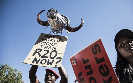 South African Federation of Trade Unions member holds a placard that mocks President Cyril Ramaphosa, where they described the proposed minimum wage as an insult to workers on 25 April 2018. Picture: Sethembiso Zulu/EWN