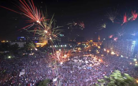 Fireworks light up the sky as hundreds of thousands of Egyptians celebrate after Egytptian Defense Minister Abdel Fattah al-Sisi's speech announced the ousting of Islamist President Mohamed Morsi in Egypt's landmark Tahrir square on3 July, 2013 in Cairo, Egypt. Picture: AFP/Khaled Desouki