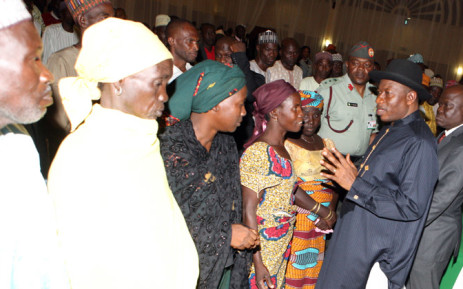 Nigerian President Goodluck Jonathan (R) speaks to some of the Chibok schoolgirls who escaped Islamist captors and relatives of the hostages during a meeting at the presidency in Abuja on 22 July, 2014. Picture: AFP.