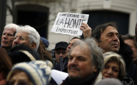 """A demonstrator holds a sign reading """"Conference of shame"""" during a rally in Paris on January 15, 2017 against the Paris Middle East peace conference. Picture: AFP"""