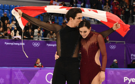 Canada's Scott Moir kisses Canada's Tessa Virtue while holding the Canada flag after they won the gold during the free dance of the figure skating event during the Pyeongchang 2018 Winter Olympic Games on February 20, 2018. Picture: AFP