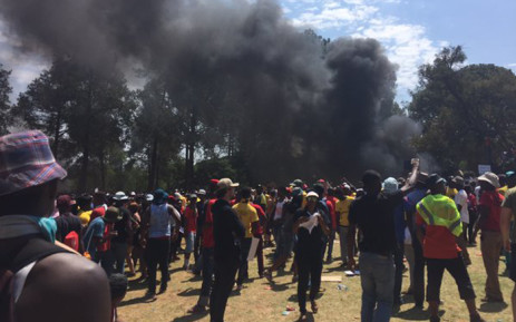 Dark smoke billows from the crowd where thousands of students have gathered at the Union Buildings, calling on President Jacob Zuma to come out to address them on 23 October 2015. Picture: Barry Bateman/EWN.