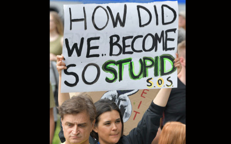 "A protester holds up a sign reading ""How did we become so stupid "" during a ""Fridays for Future"" demonstration in Berlin to protest for climate action in Berlin, on July 19, 2019. Launched by Swedish activist Greta Thunberg, ""Fridays for Future"" has seen pupils ""strike"" against school teaching each Friday for months across Europe. Picture: AFP."