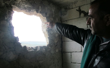 A Syrian man points to a hole in his wall after his town was attacked. Picture: Rahima Essop/EWN.