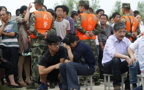 This photo taken on 3 June, 2015 shows a relative (centre R) of a passenger - missing after a Chinese cruise ship capsized on the Yangtze river - wiping away tears as relatives gather at the disaster site in Jianli, in central China's Hubei province. Picture: AFP.
