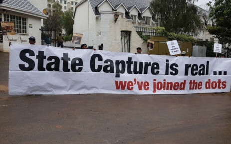 Demonstrators hold up a poster during a protest against McKinsey over 'irregular payments' involving Eskom and Trillian on 5 October 2017. Picture: Supplied.