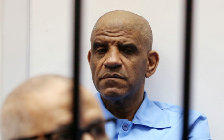 FILE: Former Libyan intelligence chief Abdullah Senussi (back) sits dressed in prison blue behind the bars of the accused cell during his trial on 28 July 2015 at court of appeals in the Libyan capital, Tripoli. Picture: AFP.