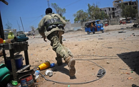A Somali soldier runs for cover at the scene of two explosions set off near the ministries of public works and labour in Mogadishu on 23 March 2019. Picture: AFP