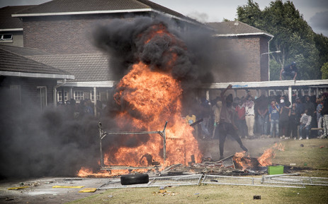 A student adds fuel to the bonfire during violent clashes between police and students at the University of the Western Cape. Picture: Thomas Holder/EWN