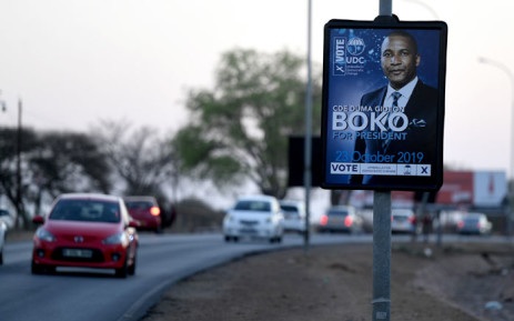 Cars pass by a poster of the president of Umbrella for Democratic Change (UDC) Duma Boko during an election campaign in Gaborone on 18 October 2019 for the general elections. Picture: AFP
