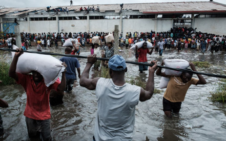 "People take part in the looting sacks of Chinese rice printed ""China Aid"" from a warehouse which is surrounded by water after cyclone hit in Beira, Mozambique, on 20 March 2019. Picture: AFP"