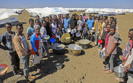 Ethiopian refugees, who fled the Tigray conflict, gather to receive aid at the Tenedba camp in Mafaza, eastern Sudan on 8 January 2021, upon their arrival at the camp from the reception center. Picture: Ashraf Shazly/AFP