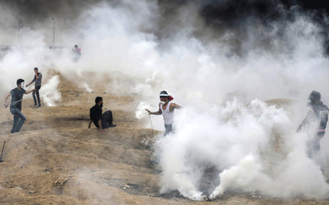 Palestinian protesters flee from teargas fumes during clashes with Israeli forces along the border with the Gaza strip east of Gaza City on 4 May 2018. Picture: AFP.