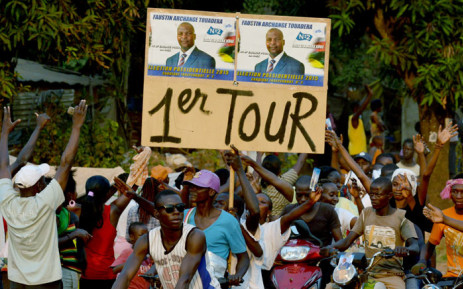 """Supporters of Central African presidential candidate Faustin Archange Touadera hold a placard with Touedara's campaign poster and reading """"1st tour"""" during a presidential campaign rally in Bangui on 28 December 2015, on the last day of campaigning ahead of Central African Republic presidential and legislative elections. Picture: AFP."""